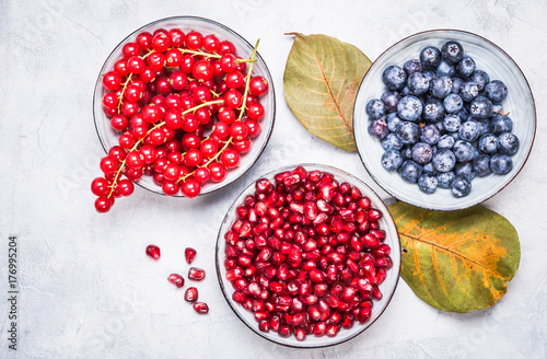 Purple and red color fruits in bowls top view.Berries, pomegranate, redcurrant winter fruits healthy snack.