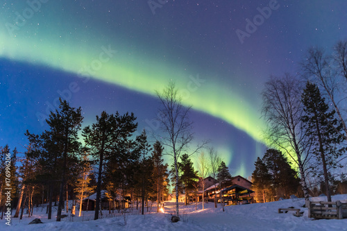 Fotobehang Noorderlicht Green Northern lights belts in a blue sky over a cottage in the lapland forest