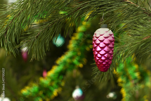 vintage glass Christmas ornament - purple fir cone - on a background of a blurred Christmas tree