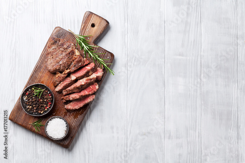 Plexiglas Steakhouse Grilled beef steak with spices on cutting board