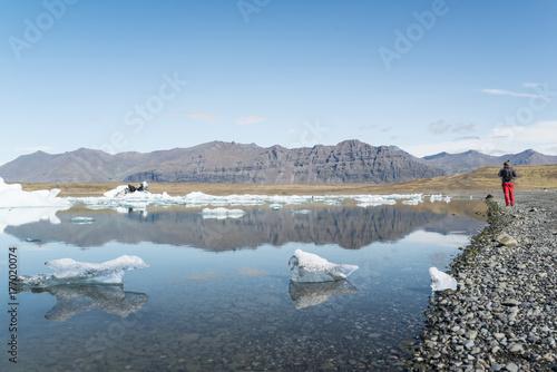 Fotobehang Een Hoekje om te Dromen Hombre caminando alrededor del lago glaciar Jokulsarlon en Islandia