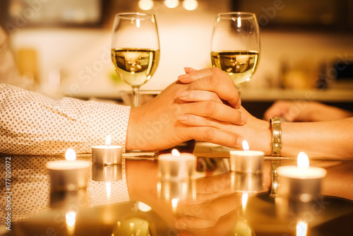 Couple drinking wine and holding hands. Poster