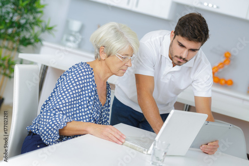 Poster elder woman sitting and learning how to use laptop