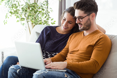 Beautiful young couple using laptop on the sofa at home.