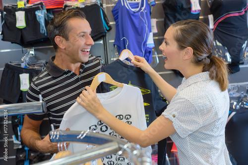 customers choosing t-shirts in a sports shop