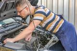 Mechaniker schaut sich den Motorraum eines Autos an - 177038428