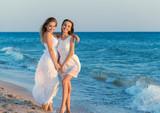 Two women in a white dress on beach