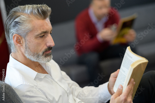 Man reading book in waiting room Poster
