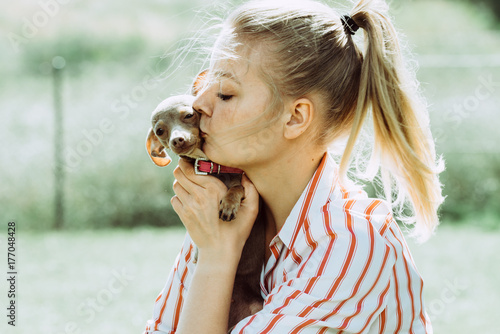 Woman playing with little dog outside Poster