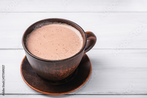 Canvas Chocolade Hot cocoa with milk in brown clay cup, on table of white wooden planks