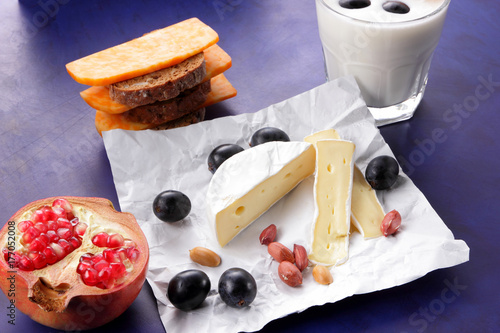 Wall mural Camembert cheese, orange marble cheese, a glass of milk, pomegranate, olives, peanut grains, dark blue grapes and bread on white fabric and dark blue background, cheese background in retro style