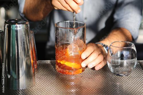 Barkeeper bereitet mischt einen Cocktail