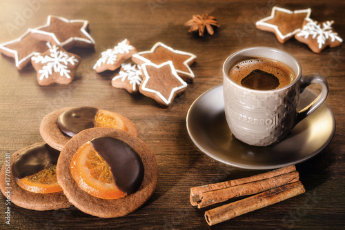 Wall mural Coffee drink with gingerbread on a wooden background. A cup of hot coffee with New Year cookies in the sun.