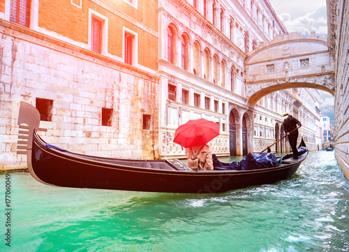 Plakat Female traveler in Gondola passing over Bridge of Sighs in Venice