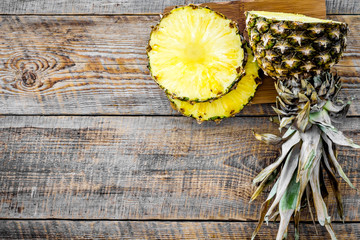 Sliced pineapple on wooden background top view copyspace