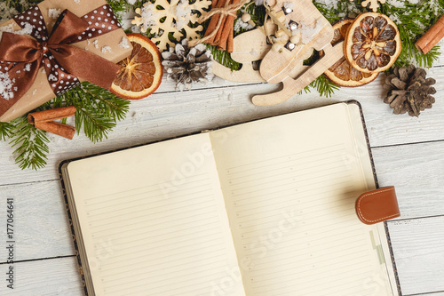 Christmas ornaments and an open blank notebook on a light wooden table плакат