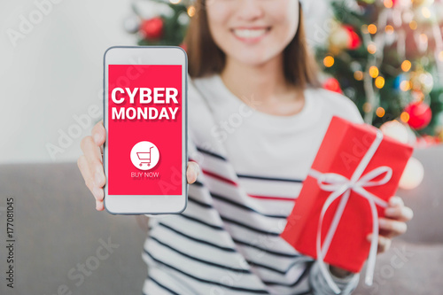 Young beautiful Asian Woman hands holding gift box and smartphone with cyber Monday screen.Smile face in room with Christmas tree decoration for holiday background.