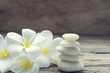 Pile of white zen stones and Frangipani flower on rustic wood background,retro effect