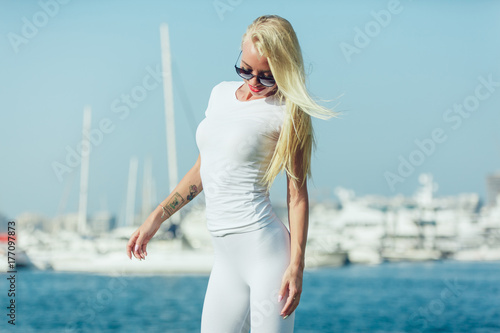 Plakát Sexy blonde woman in a white T-shirt is standing in the port