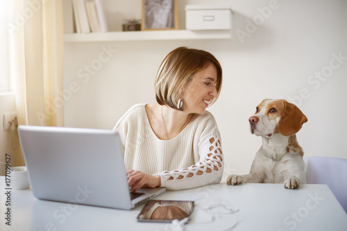 Wall mural Freelancer using laptop for working, dog next to her