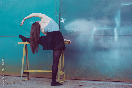 Young ballerina in black clothes training in front of the turquoise blue door Poster