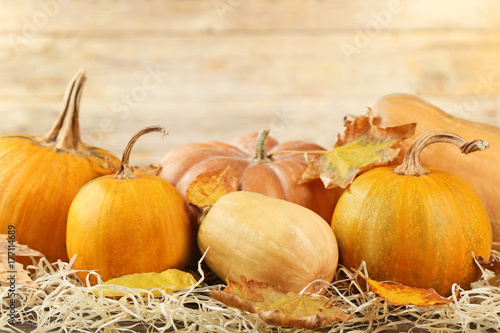 Orange pumpkins with dry leafs on grey wooden table