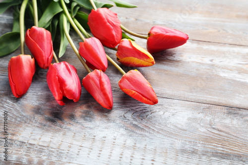 Bouquet of red tulips on grey wooden table