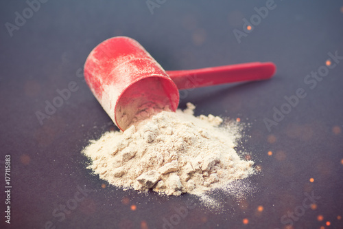 Fitness and sports concept with a spilled scoop of protein powder necessary nutr Poster