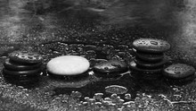 Spa stones on a dark background with water drops and reflection