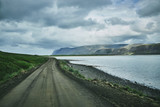 Travel to Iceland. plot of asphalt road in a dark cloudy mountain landscape. focus on the road - 177124243