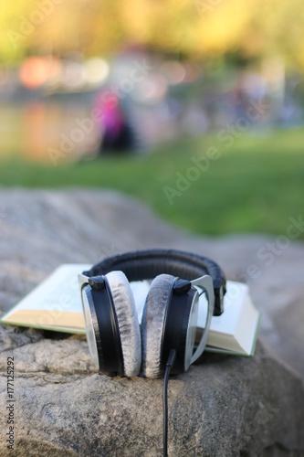 Kopfhörer auf einem Buch - Assoziation: Hörbuch, Hörbücher, Audiobook Poster