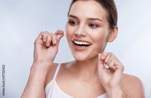 Woman cleaning teeth with tooth thread