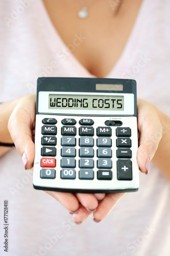 Cost of wedding concept with calculating machine in woman hand spelling wedding cost on digital display - 177128410