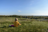 small child in bright clothes, sitting on a high hill opens a beautiful view - 177129050