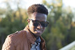 Handsome young black man in sunglasses and a leather jacket on a fall day