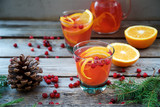 Warm cranberry drink with oranges and cinnamon. Wooden background   - 177134097