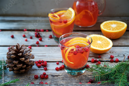 Warm cranberry drink with oranges and cinnamon. Wooden background