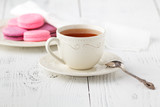 Colorful French macaroons and cup of tea on a rustic wooden background, selective focus - 177141247