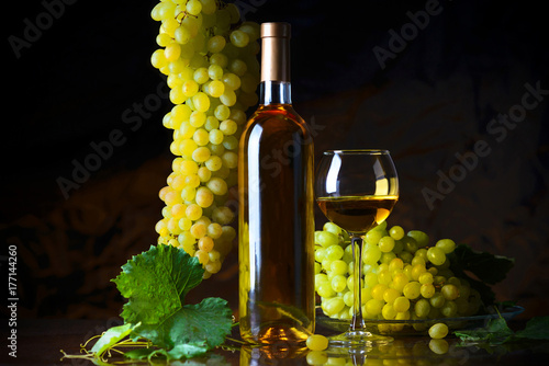 The composition of bottle glass of white wine and fresh grapes