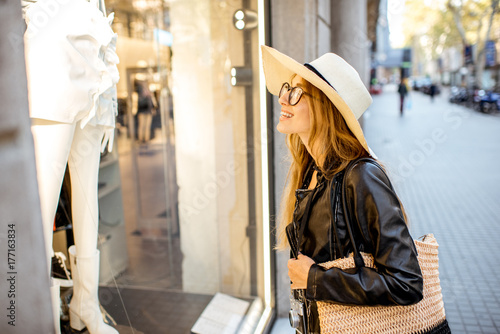 Young woman looking on the showcase of the fashion store on the street in Barcelona
