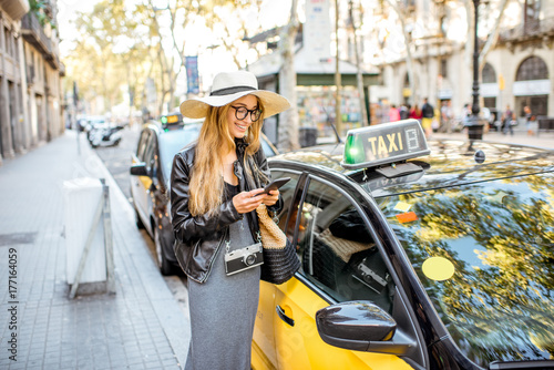 Young woman tourist using a smart phone standing near a taxi car on the street in Barcelona city