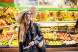 Woman standing in front of the food store showcase with fruits and vegetables - 177164248