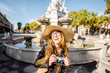 Portrait of a young woman tourist with photocamera standing near the fountain in Barcelona city