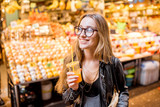 Young woman drinking orange juice in the famous food market in Barcelona city - 177164858