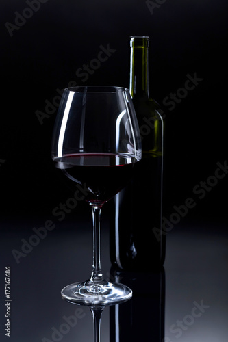 Glass and bottle of red wine.