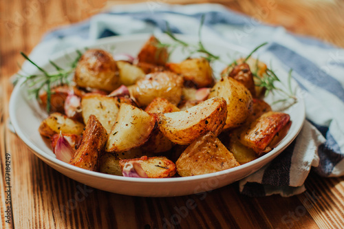 Roasted potato in white plate on wooden background with rosemary and garlic