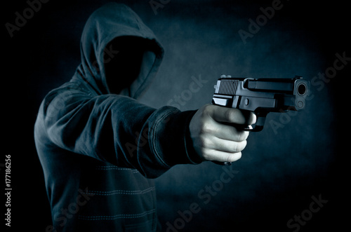 Hooded man with a gun in the dark Poster