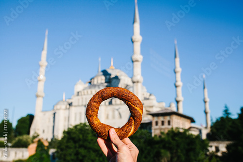 A woman is holding a traditional iretsky bagel named Simit in the background of the Blue Mosque in Istanbul, Turkey Poster