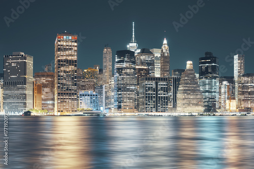 New York City skyline seen from Brooklyn at night, color toning applied, USA.
