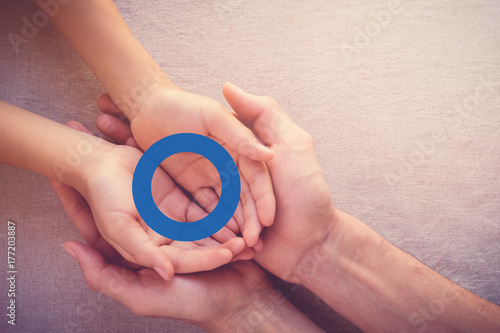 Foto Murales adult and child holding blue circle, copy space background, World Diabetes day